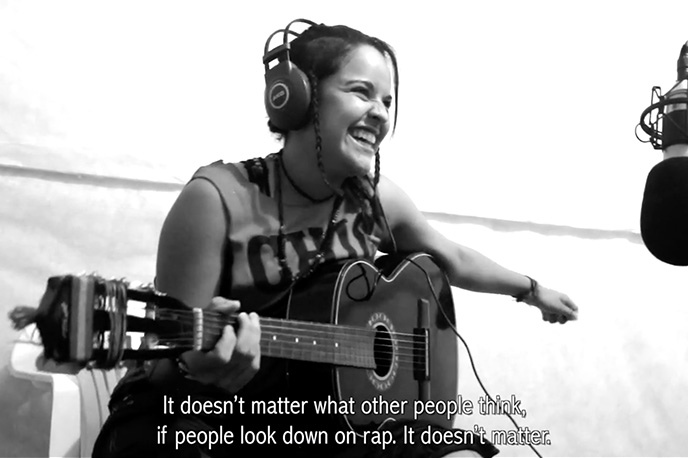 UT alumna Jessica Diaz-Hurtado playing the guitar while wearing headphones.