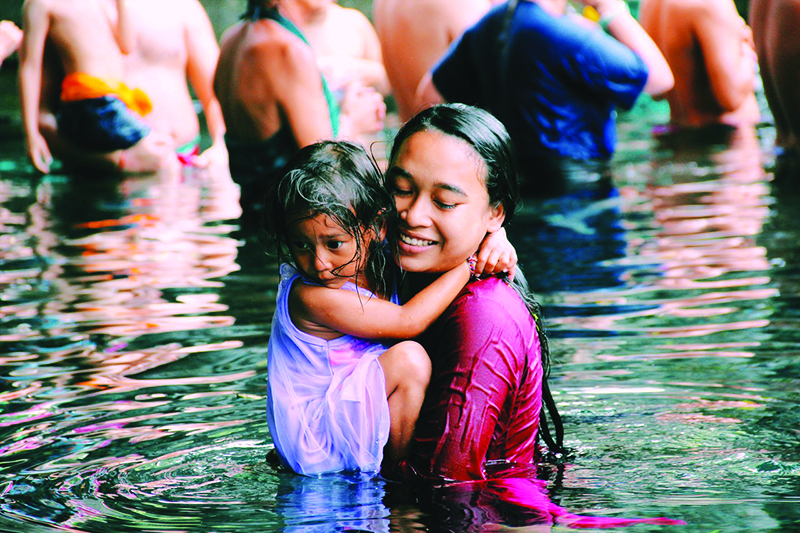 Photo of smiling woman holding child while wading in water in Bali, Indonesia.