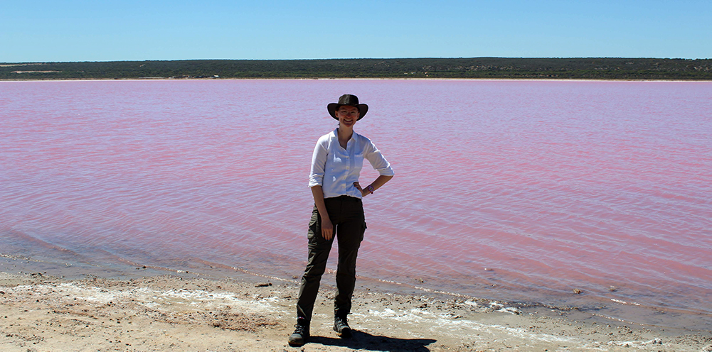 Ally poses in front of the pink lake in australia