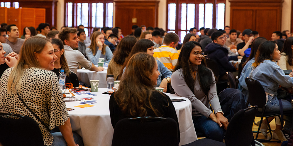 An international student asked questions to volunteers at Orientation