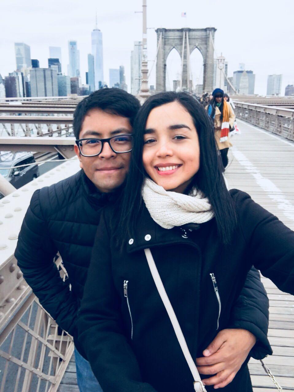 eduardo and paulina pose on the brooklyn bridge