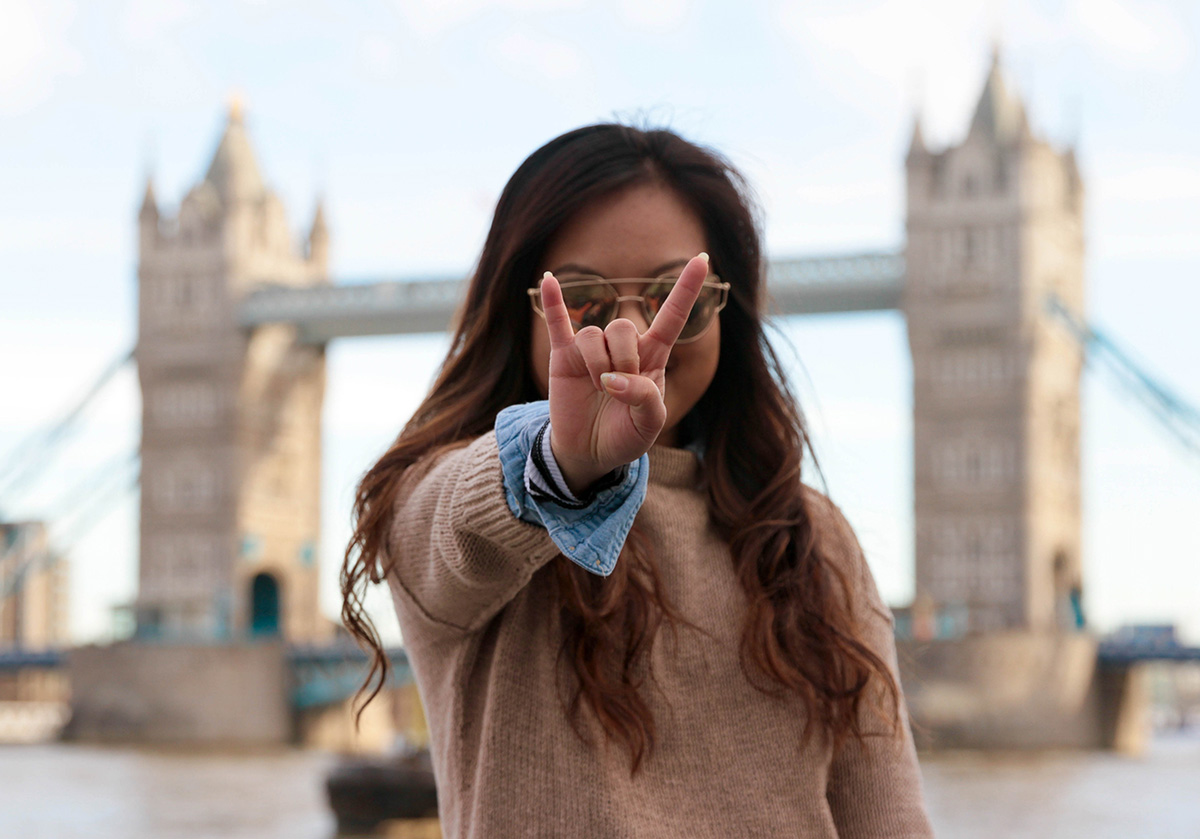 A girl doing a hook 'em horns in front of the London Tower Bridge