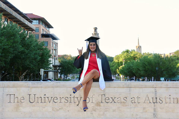 Marielisa on a UT sign with her graduation cap and gown