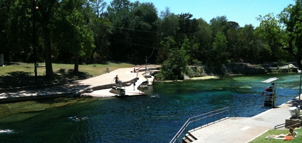 A swimmer prepares to jump off a diving board at Barton Springs pool.