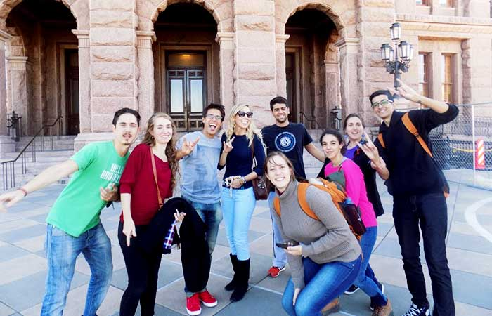 A group of students pose and give the hook em horns hand sign in front of a building.