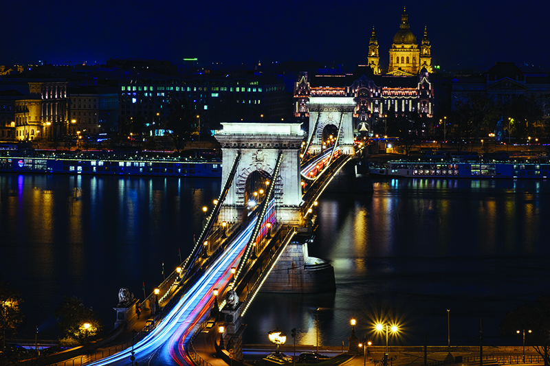 Photo of bridge and building lights at night in Budapest, Hungary.