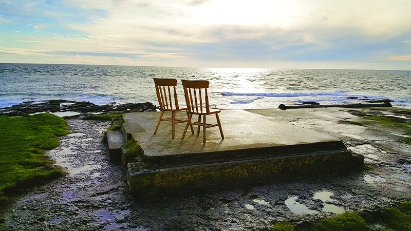 Photo of two wooden chairs on slab of concrete on beach in Hook Head, Ireland.