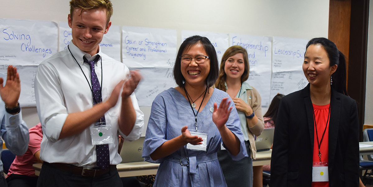 The seminar group plays the name game—clapping at each person in the circle while saying their name—to get to know each other on the first day of the conference.