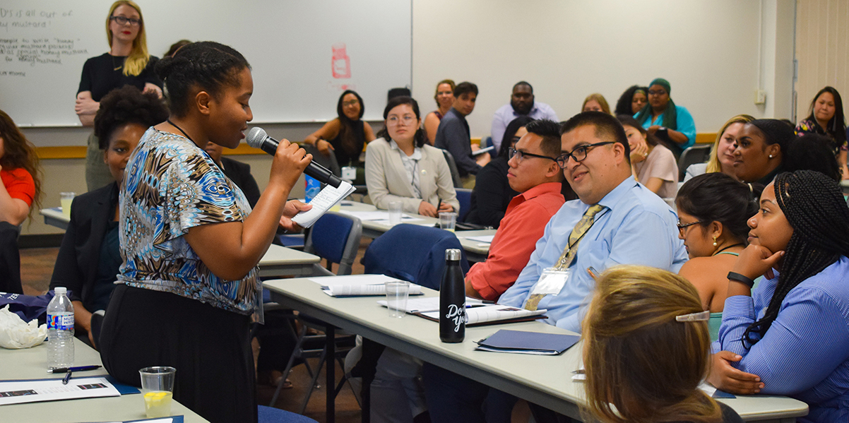 An alumna presents her elevator pitch for a startup idea to conference attendees. The alumni developed one-minute pitches with 3 Day Startup instructors to strengthen their entrepreneurial thinking.