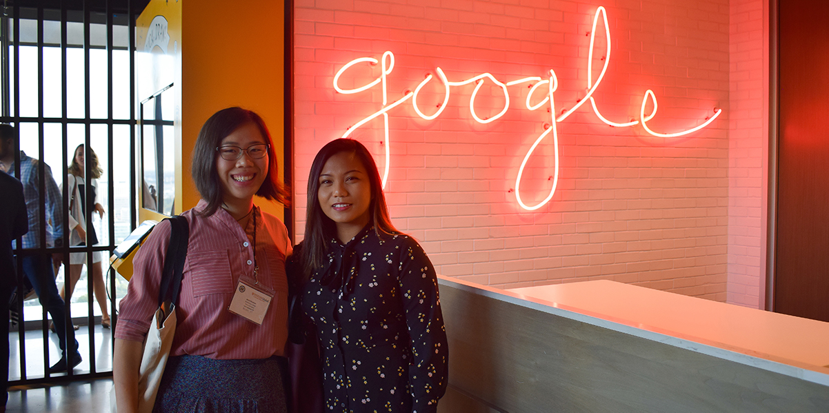 Two alumnae pose with the Google logo before their tour of the site