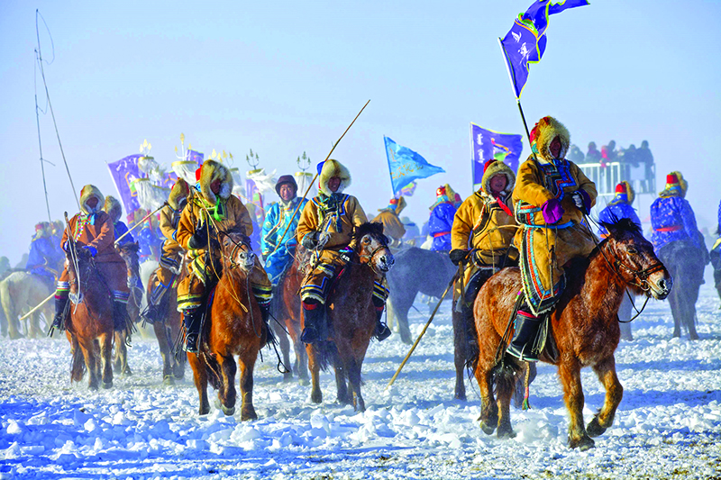 Photo of people carrying flags while riding donkeys through the snow in Ulaanbaatar, Mongolia.