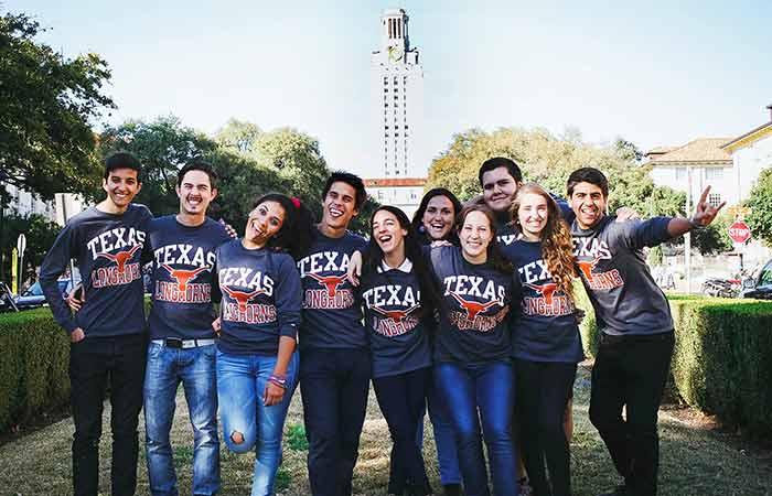 A group of students pose in front of the UT tower.