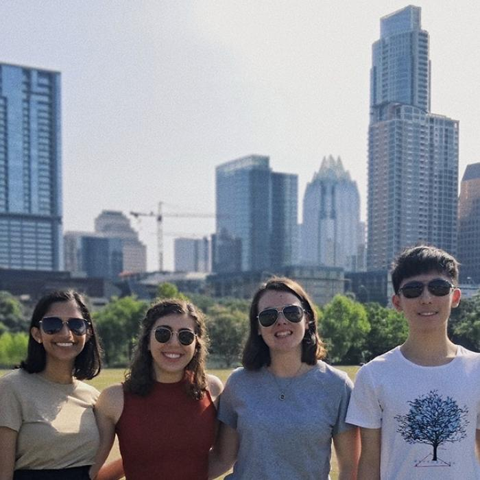 students stand in front of city skyline