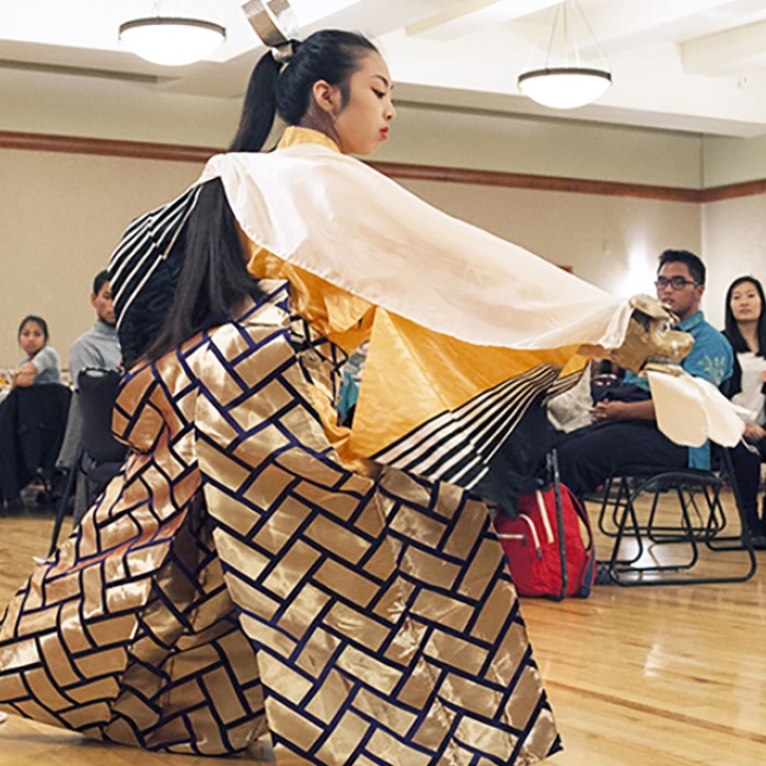Asian dancer in traditional clothing on UT campus