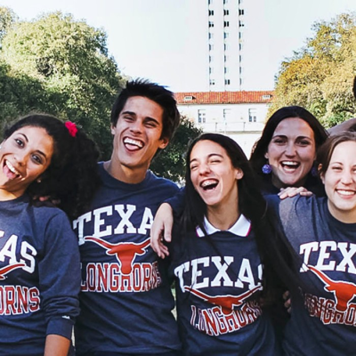 A group of students smile and link arms wearing matching Texas t-shirts in front of the tower.