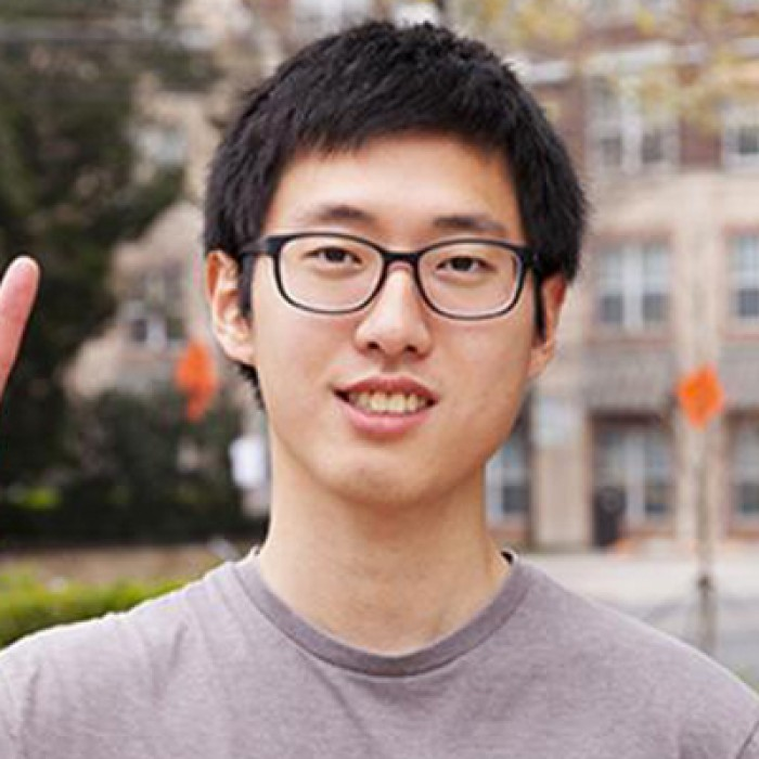Exchange Student Chen Pang Chang gives the hook 'em horns sign while standing in front of the Texas Global building.