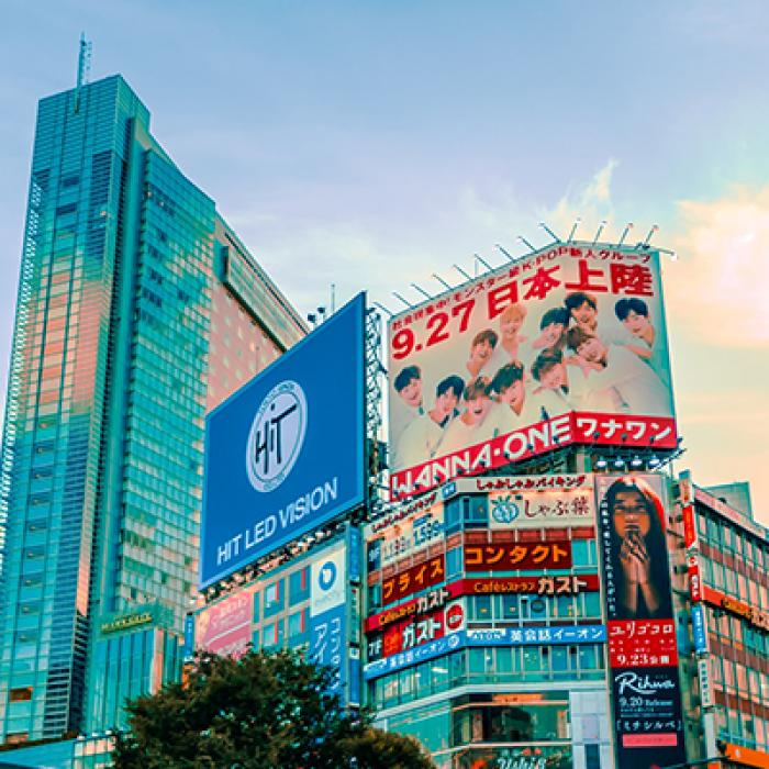 Buildings, billboards against a blue sky in Tokyo.