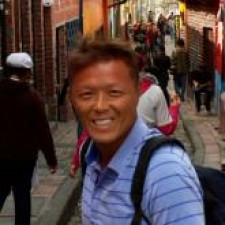Larry Phu outside on a busy town street, wearing a travel backpack and smiling into camera, his hair blowing in the wind.