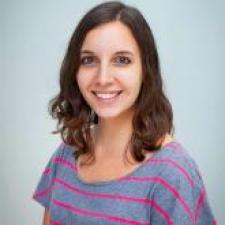 Headshot of Victoria Lamb wearing casual striped t-shirt and smiling into camera against gray background.