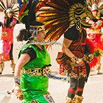 Mexican dancers in cultural dress and wearing masks