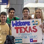 "UT administrators and students hold a sign that reads ""Welcome to Texas Fulbright Argentina Scholars"" at the Austin airport."