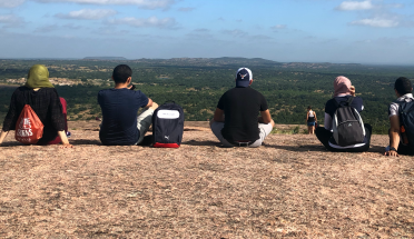 six visiting egyptian faculty sit on enchanted rock in austin