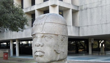 the olmec head statue in front of a building on campus