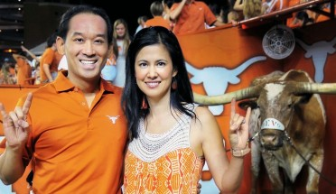 andrew vo stands with wife sophie at a texas game