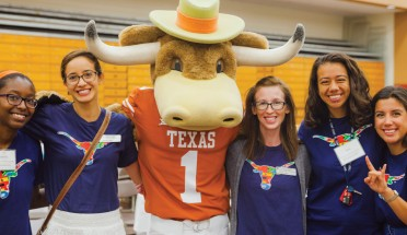 students stand with the hook em mascot at UT