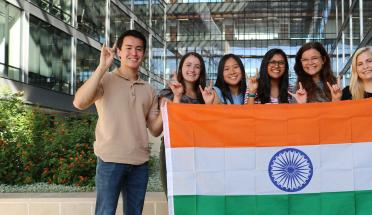 group of students hold up Indian flag near building outside during daytime
