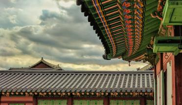 brown and green pagoda during daytime with cloudy sky