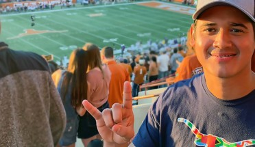 jaime ortega poses at a ut football game in the stadium