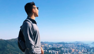 a student stands on a mountain overlooking a city in China
