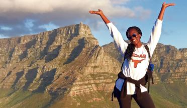 a student poses on a mountain and smiles