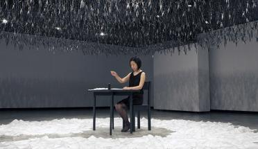 woman works at table in large studio space with sculpture art above and below